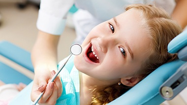 Little girl smiling in dental exam chair