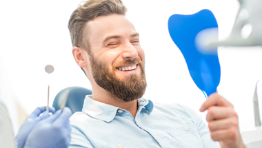 Man in dental chair looking at smile in mirror
