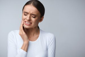 A woman experiencing dental pain.