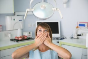 A woman covering her mouth at the dental office.