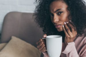 woman with tooth sensitivity drinking coffee