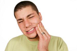Grimacing man holding cheek in pain